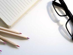 משקפי ראייה לצד מחברת ומספר עיפרונות