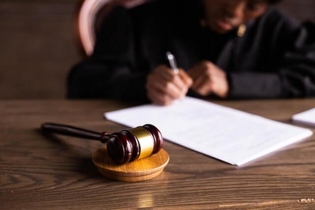פטיש בית משפט על גבי שולחן ועורכת דין חותמת על מסמך