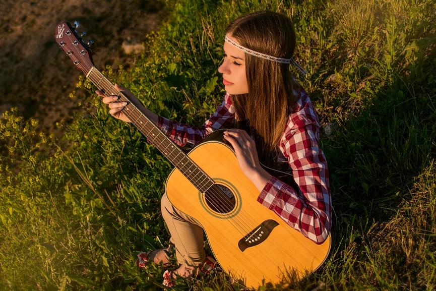 אישה מחזיקה גיטרה